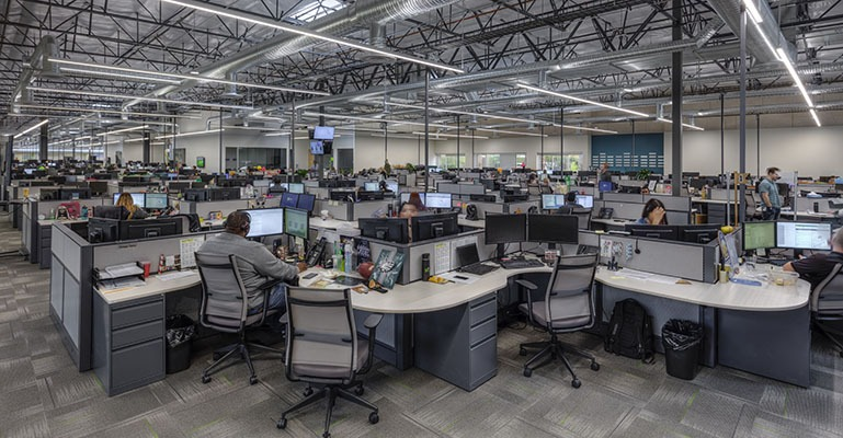 Numerous office employees are seated in cubicles in a busy office space.