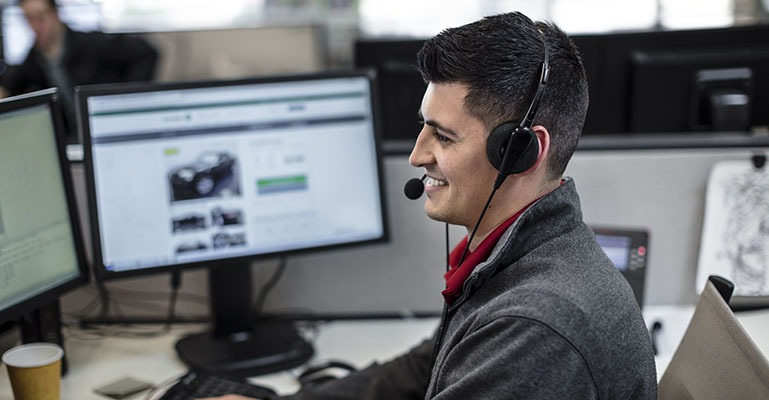 A help desk employee wearing a headset smiles while talking to a customer.