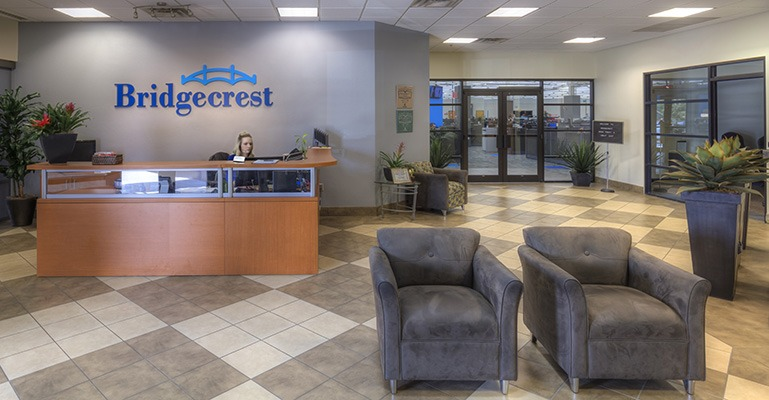 A receptionist sits behind a desk in a large, welcoming foyer area with the Bridgecrest logo on the wall.