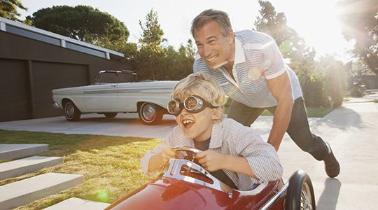 A smiling and laughing child rides in a toy car with an older man pushing it forward.
