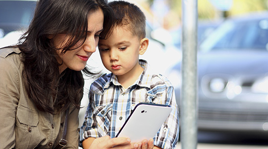 A young mother and son look at a smartphone screen together, with a parking lot visible through a window behind them.