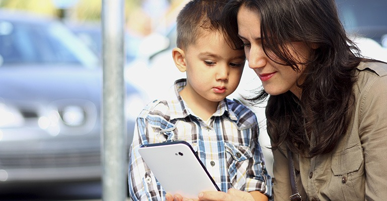 A young mother and her young son look at a tablet together.