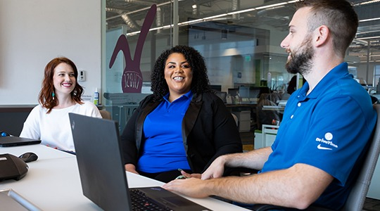 Three UnitedHealthcare Health Advocates smile and talk to each other behind a desk while waiting for a customer to call.