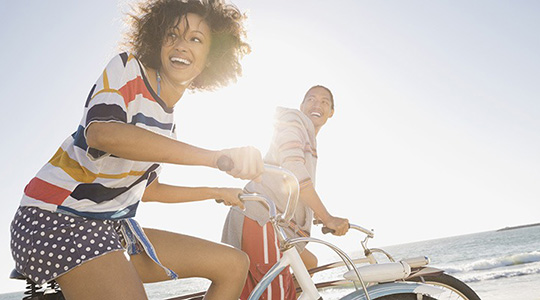 A young man and young woman riding bikes on a beach turn to the right and grin.