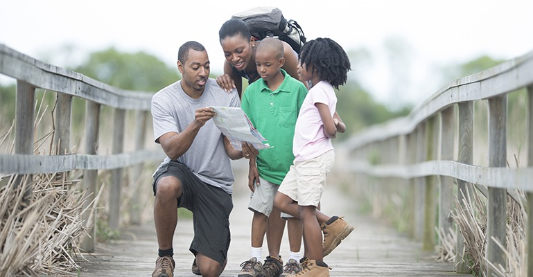 A family of four stops in the middle of an old, weathered pedestrian bridge to check their map.