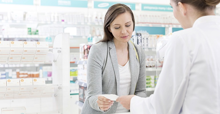 A pharmacist and customer look at a prescription together.