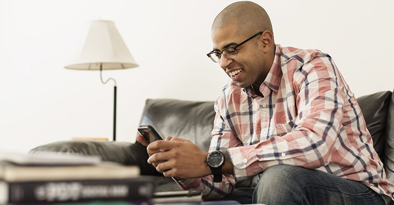A smiling man sits on a couch, looking at his smartphone screen.