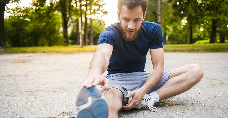 A young man stops in the middle of a run down an outdoor path to stretch his legs.