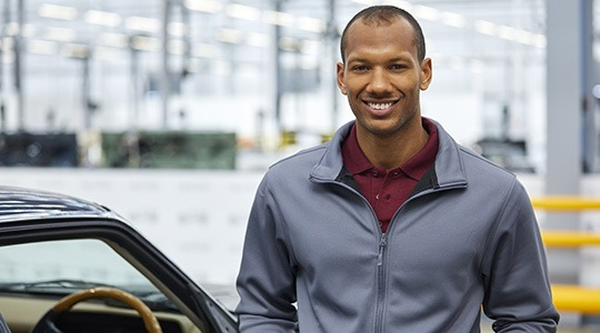 A smiling man in a zip-up jacket stands next to a car, with a cityscape in the background.