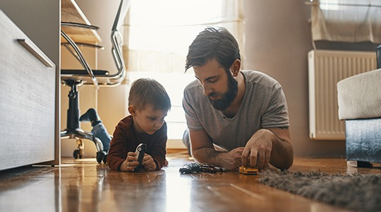 A young father and his small child play with toy cars on the floor.