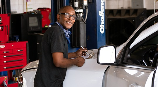 A bespectacled mechanic writes on a clipboard placed on the hood of a white car in a garage.
