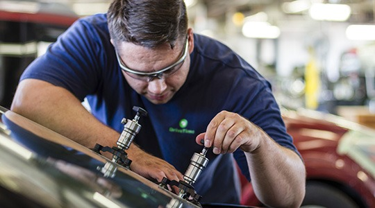 A man wearing goggles in a body shop works on removing a dent from a car.