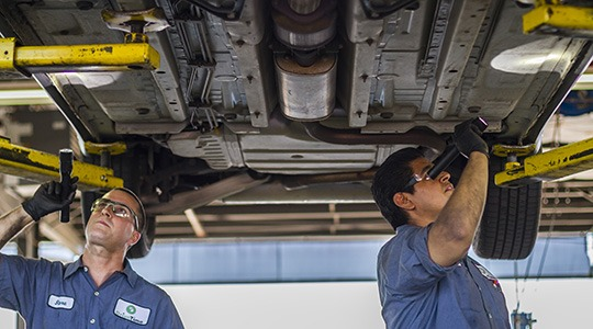 Two mechanics with flashlights work on the underside of a large vehicle.