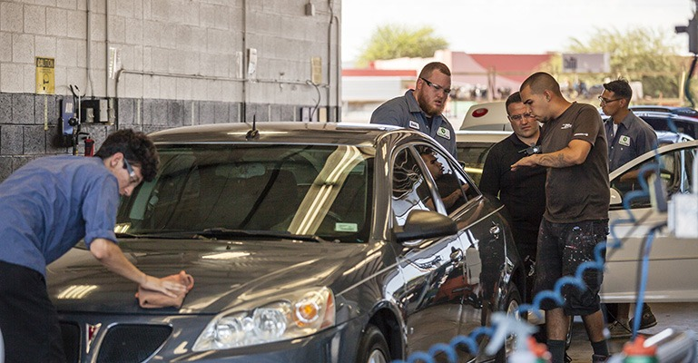 A group of workers at a body shop work on polishing a grey car.